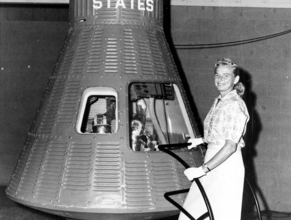Jerrie Cobb standing next to a Mercury capsule.